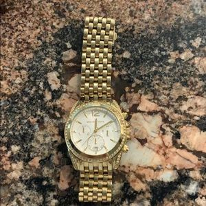 Michael Kors gold watch with white face.